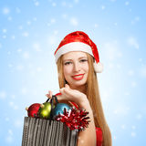 圣诞老人帽子的少妇有圣诞节属性和礼物的 库存照片