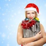 圣诞老人帽子的少妇有圣诞节属性和礼物的 图库摄影