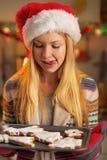 圣诞老人帽子的少年女孩有平底锅的曲奇饼 库存图片