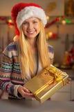 圣诞老人帽子的少年女孩有当前箱子的 免版税图库摄影