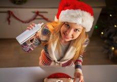 圣诞老人帽子的少年女孩有打好的奶油的 免版税库存照片