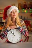 圣诞老人帽子的少年女孩有时钟的 免版税图库摄影