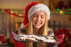 圣诞老人帽子的少年有平底锅的新鲜的曲奇饼 图库摄影