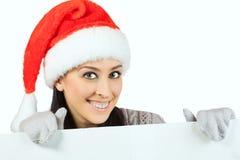 圣诞老人帽子的微笑的女孩。隔绝 免版税库存照片