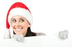 圣诞老人帽子的微笑的女孩。 查出 库存图片