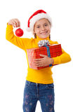 圣诞老人帽子的微笑的女孩与红色配件箱 库存照片