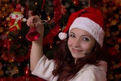 圣诞老人帽子的微笑的妇女有响铃的 图库摄影
