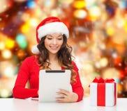 圣诞老人帽子的微笑的妇女有礼物和片剂个人计算机的 库存照片
