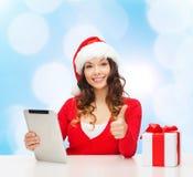 圣诞老人帽子的微笑的妇女有礼物和片剂个人计算机的 免版税图库摄影