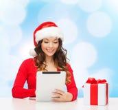 圣诞老人帽子的微笑的妇女有礼物和片剂个人计算机的 免版税库存照片