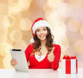 圣诞老人帽子的微笑的妇女有礼物和片剂个人计算机的 库存图片