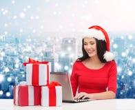 圣诞老人帽子的微笑的妇女有礼物和膝上型计算机的 免版税库存图片