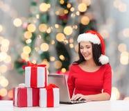 圣诞老人帽子的微笑的妇女有礼物和膝上型计算机的 免版税库存照片