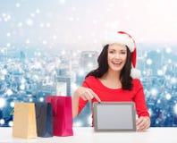 圣诞老人帽子的微笑的妇女有袋子和片剂个人计算机的 库存图片