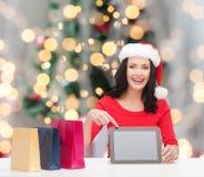 圣诞老人帽子的微笑的妇女有袋子和片剂个人计算机的 库存照片