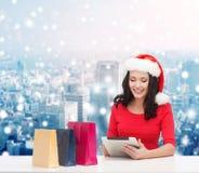 圣诞老人帽子的微笑的妇女有袋子和片剂个人计算机的 免版税库存照片