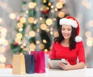 圣诞老人帽子的微笑的妇女有袋子和片剂个人计算机的 图库摄影