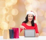 圣诞老人帽子的微笑的妇女有袋子和片剂个人计算机的 免版税图库摄影