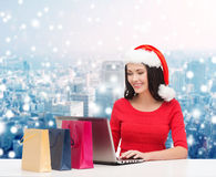 圣诞老人帽子的微笑的妇女有袋子和膝上型计算机的 库存照片