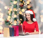 圣诞老人帽子的微笑的妇女有袋子和膝上型计算机的 免版税库存图片