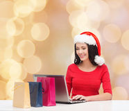 圣诞老人帽子的微笑的妇女有袋子和膝上型计算机的 免版税图库摄影