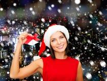 圣诞老人帽子的微笑的妇女有门铃的 库存图片