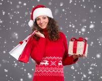 圣诞老人帽子的微笑的妇女有购物袋和礼物盒的 库存图片