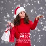 圣诞老人帽子的微笑的妇女有购物袋的 库存照片