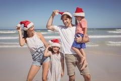 戴圣诞老人帽子的微笑的家庭在海滩 免版税库存照片