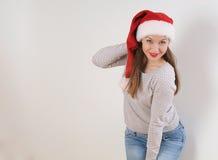 圣诞老人帽子的微笑的少妇在白色背景 库存图片