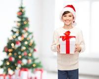 圣诞老人帽子的微笑的愉快的男孩有礼物盒的 免版税图库摄影
