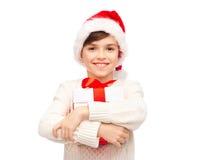 圣诞老人帽子的微笑的愉快的男孩有礼物盒的 免版税库存照片