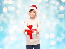 圣诞老人帽子的微笑的愉快的男孩有礼物盒的 库存图片