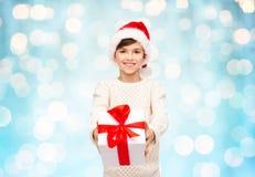 圣诞老人帽子的微笑的愉快的男孩有礼物盒的 库存照片