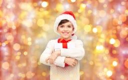 圣诞老人帽子的微笑的愉快的男孩有礼物盒的 图库摄影