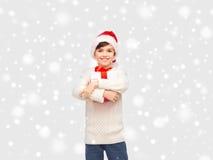 圣诞老人帽子的微笑的愉快的男孩有礼物盒的 免版税库存图片