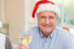 圣诞老人帽子的微笑的成熟人敬酒用白葡萄酒的 免版税库存图片