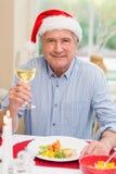 圣诞老人帽子的微笑的成熟人敬酒用白葡萄酒的 库存照片