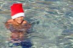 圣诞老人帽子的微笑的男孩在海 免版税库存照片