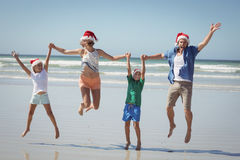戴圣诞老人帽子的快乐的家庭,当跳跃在海滩时 库存照片