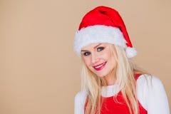 戴圣诞老人帽子的快乐的白肤金发的妇女 免版税库存照片