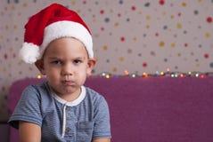 圣诞老人帽子的恼怒的男孩 免版税库存照片