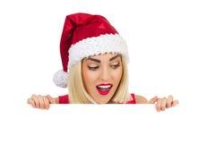 圣诞老人帽子的惊奇的白肤金发的女孩 库存照片
