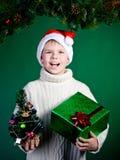 圣诞老人帽子的惊奇的滑稽的男孩有礼物的。新年。圣诞节。 库存照片