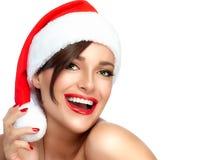 圣诞老人帽子的愉快的圣诞节女孩 美好的大微笑 图库摄影