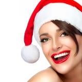 圣诞老人帽子的愉快的圣诞节女孩 美好的大微笑 免版税库存图片
