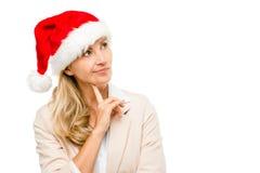 戴圣诞老人帽子的愉快的女实业家认为圣诞节isol 库存图片