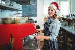 戴圣诞老人帽子的愉快的女服务员画象在咖啡馆 图库摄影
