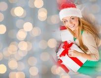 圣诞老人帽子的愉快的妇女有圣诞节礼物的 免版税库存照片