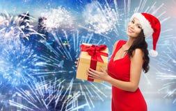 圣诞老人帽子的愉快的妇女有在烟花的礼物的 库存图片
